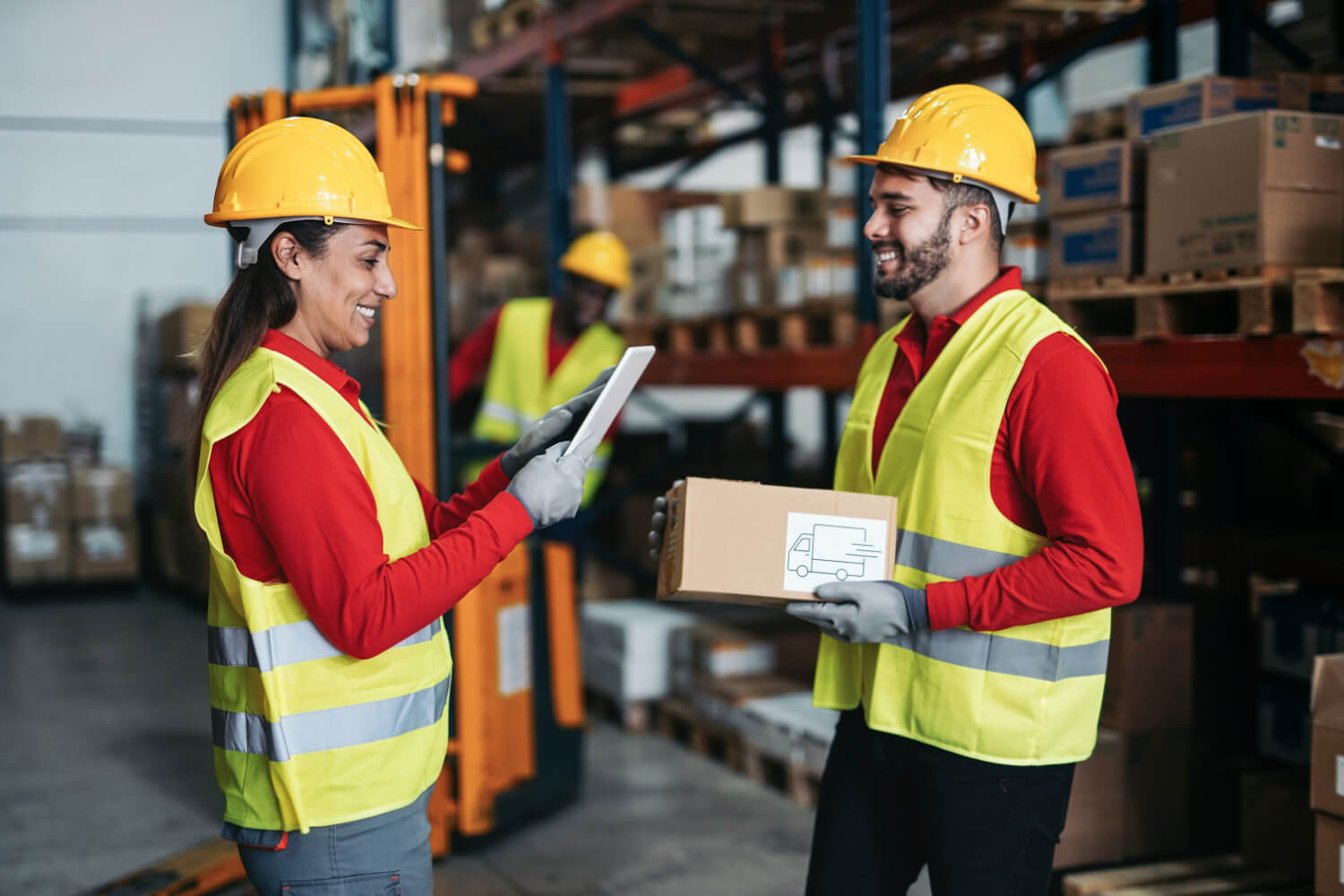 Multiracial warehouse worker with package and digital tablet